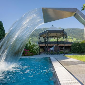 Heated outdoor pool with neck massage waterfall